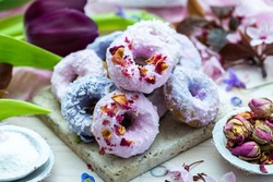 Table top scene of colorful doughnut cookies with edible flowers and birch sugar. Donut cookies. Pink and blue round raw cookies. Raw food, vegan menu. Black tulips.