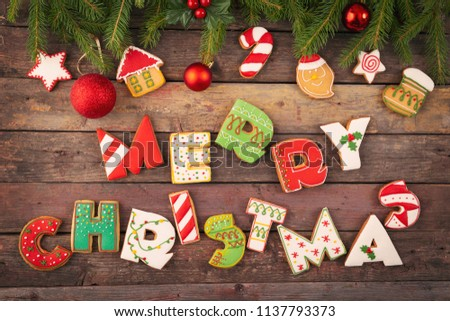 Table top shot of colorful gingerbread cookies shaped like letters Merry Christmas and Christmas tree decorations on fir tree branches #1137793373