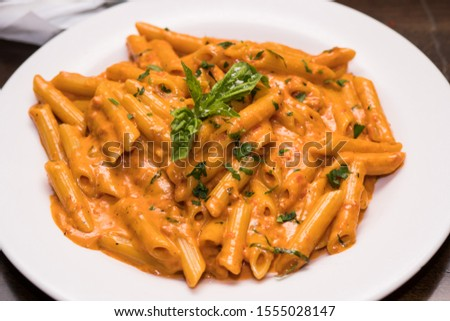 Table top shot of delicious beautiful prepared bowl of penne ala vodka noodles in pink tomato sauce at a gourmet restaurant ストックフォト ©