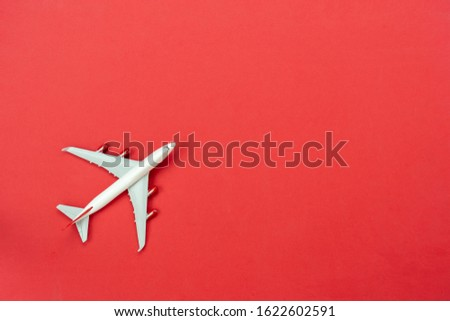 Table top view accessory of accessory travel in holiday background concept.Flat lay of white airplane on modern rustic red paper at home studio office desk.copy space for creative design text.