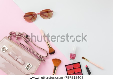 Table top view accessory of clothing women plan to travel in holiday background.Beauty & Fashion concept.Flat lay Hand bag with many essential  items cosmetic and sun glasses on modern pink paper.