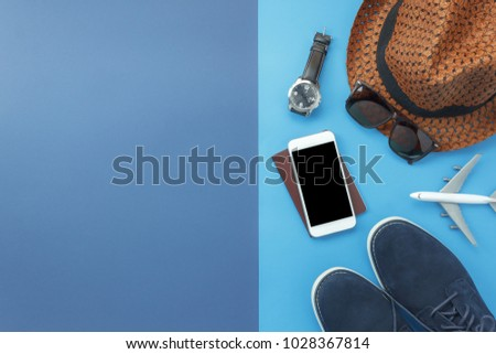 Table top view accessory of clothing women  plan to travel in holiday background concept.Mobile phone with many essential  items hat & shoes on modern rustic duo blue paper with space creative design.