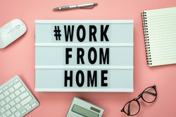 Table top view aerial image of accessories office desk for work from home with # WORK FROM HOME text background concept.Flat lay of notebook & keyboard and calculator with face mask on pink paper.