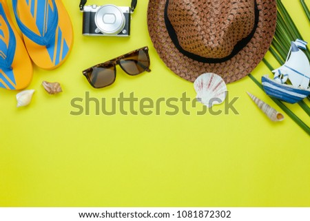 Table top view aerial image of accessory for summer travel holiday background.Flat lay essential objects for beach vacation on modern yellow paper at office desk.free space for creative design text.