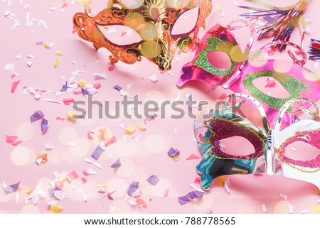 Table top view aerial image of beautiful colorful carnival mask or photo booth prop background.Flat lay object on modern rustic pink wallpaper with bokeh.Free space for creative design mock up.
