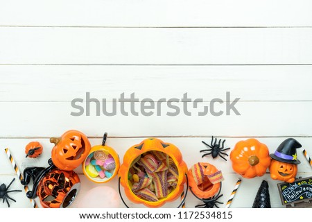 Table top view aerial image of decoration Happy Halloween day background concept.Flat lay accessories essential object to party the pumpkin & sweet candy on white wooden.Space for creative design.