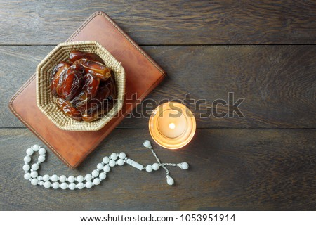 Table top view aerial image of decoration Ramadan Kareem holiday background.Flat lay date in wood basket with white rosary & lighting.The holy book of Koran on modern rustic brown wood at office desk. #1053951914