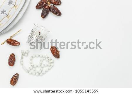 Table top view aerial image of decoration Ramadan Kareem holiday background.Flat lay date with rosary & lighting.The hat on modern rustic white wooden at office desk.Negative space creative design. #1055143559