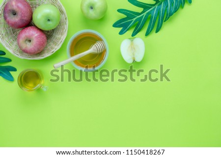 Photo of Table top view aerial image of decorations Jewish holiday the Rosh Hashana background concept.Flat lay of variety apple & honey bee and green left on modern rustic green paper.Free space for design.