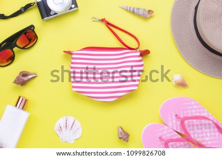 Table top view aerial image of items to travel summer holiday background concept.Flat lay essentials accessories for travel to beach trip.Fashion pink hand bag with women clothing on yellow paper.