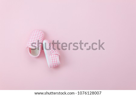 Photo of Table top view aerial image of kid fashion background concept.Flat lay shoe baby on modern beautiful rustic pink paper at office desk.Free space for creative design text and wording.Pastel tone
