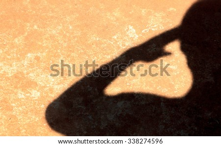 Photo of Table top view aerial image of solder background concept.Flat lay shadow sign human is saluting.on modern grunge cement floor.Free space for creative design content & font.