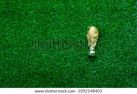 Photo of Table top view aerial image soccer or football season background concept.Flat lay accessories trophy on the artificial green grass wallpaper.Free space for creative design text and content wording.