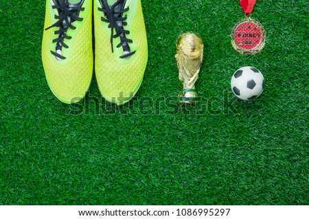 Table top view aerial image soccer or football season background.Flat lay accessories trophy & ball with shoe and medal on the artificial green grass wallpaper.Free space for design text and content. #1086995297