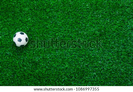Photo of Table top view aerial image soccer or football tournament season background.Flat lay object on the artificial green grass wallpaper.Free space for design mock up text and content.