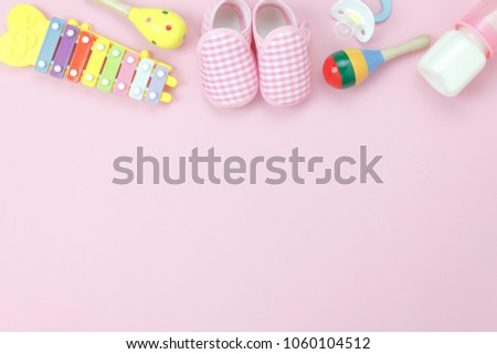 Table top view decoration kid toys for develop background concept.Flat lay baby shoes with items child on modern pink paper at office desk.Copy space for add text.Creative deign pastel tone wallpaper.