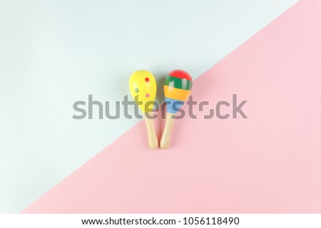 Table top view kids toys for develop background concept.Flat lay objects the colorful wooden ball percussion musical instruments on modern duo paper blue & pink at office desk.Design pastel tone.