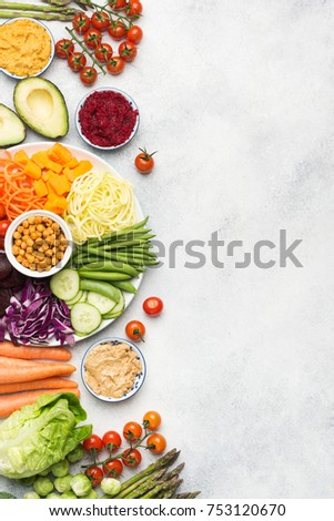 Table top view of rainbow buddha bowl, various vegetables, carrot, courgette, cabbage, chickpeas, cucumber and tomatoes, on wooden board on white table, vertical, selective focus