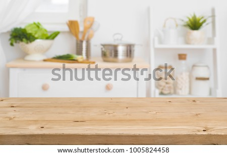 Table top with blurred kitchen furniture as background #1005824458