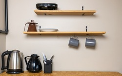 Table used for quick meals such as breakfast with a toaster, hanging mugs, water jug, electric kettle, fork, knife and spoons on a support. Casual disposition referring to family vacations.