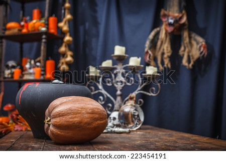 Table with a pot, pumpkin, crystal ball chandelier and to celebrate holiday halloween