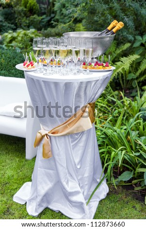 Table with champagne and appetizers at a wedding outdoors