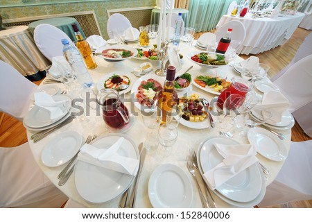 Table with dishes, a variety of drinks and snacks from the meat, vegetables and fruit.