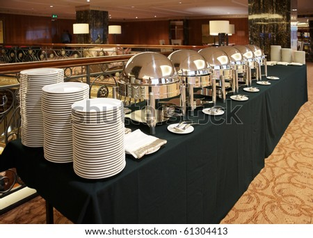 Table with dishware and shiny marmites in hotel lobby