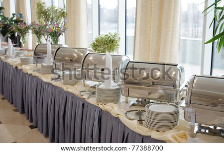 Table with dishware and shiny marmites waiting for guests