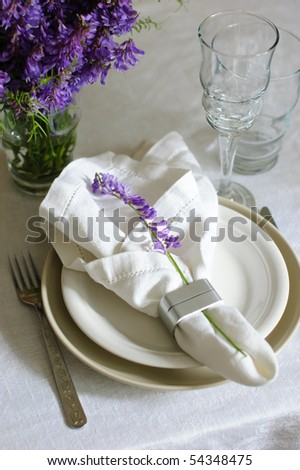 Table with elegant setting, on the white tablecloth with purple flowers