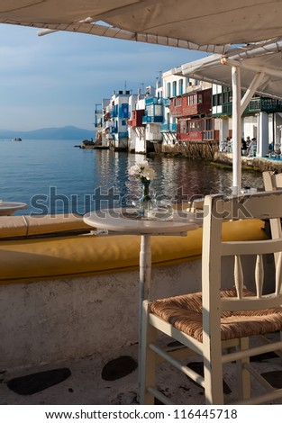 Table with flowers in cafe at Little Venice at sunset. Mykonos. Greece.