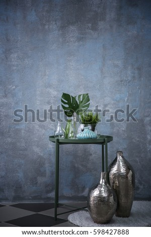 Table with home decor on grey wall background #598427888