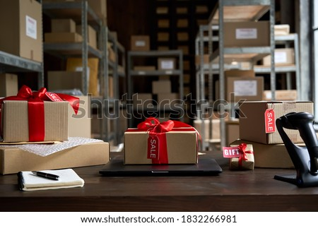 Table with laptop and gift boxes with sale tags on table in warehouse. Online ecommerce retail business black friday discounts deals, free shipping. Best buy holiday offers concept storage background.