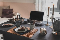 Table with laptop, cake, cookies and autumnal decoration in a cozy room prepared for virtual coffee with family or friends, useful during worldwide covid-19 pandemic quarantine times