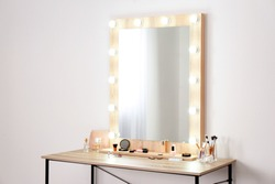 Table with makeup products and mirror near white wall, space for text. Dressing room interior