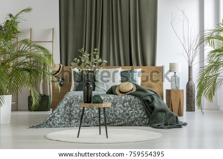 Table with plant on white round carpet and green curtain behind king-size bed with hat in bedroom with plants