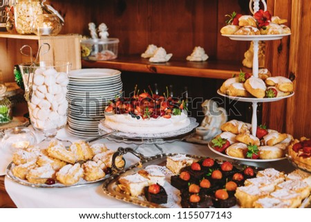 Table with sweets: cookies with strawberries, sponge cake, donuts, sweet rolls, cake. A sweet buffet at a party, an outdoor dinner, a wedding. #1155077143