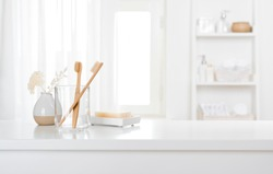 Table with toothbrushes and soap inside a bright defocused bathroom