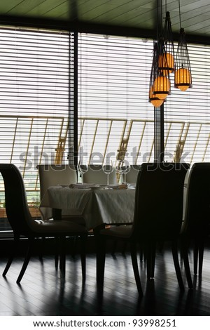 table with white tablecloth and serving and chairs in empty restaurant