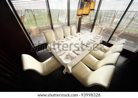 table with white tablecloth and serving and ten white chairs in empty lit restaurant