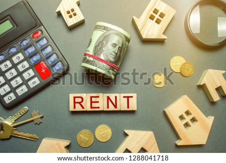 Table with wooden houses, calculator, coins, magnifying glass with the word Rent. The concept of rental housing. Rent an apartment or house. Payment for rent. Real Estate Agent Services. Realtor