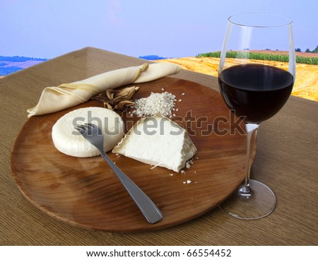 Table with wooden plate, two different kinds of cheese, rice, mushrooms and a glass of red wine