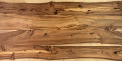 Table wooden surface from natural walnut. Rich wood grain texture background with knots and strong lines. Copy space