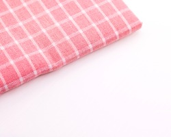 Tablecloth fabric on white background. Pink napkin or picnic textile.