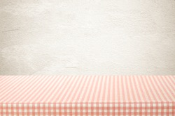 Tablecloth in pink and white pattern, perspective, over brown gradient kitchen wall background, Empty table top, shelf, counter mock up for food and product display montage, template