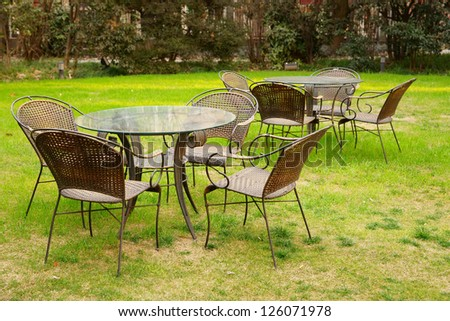 Tables and chairs in the garden at afternoon.It\'s a very beautiful view./Tables and chairs in the garden/Tables and chairs
