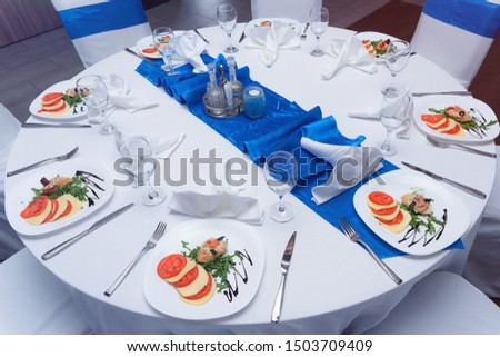 Tables and chairs in the restaurant with food and  full set preparation for dinner. Romantic dinner table setup.
