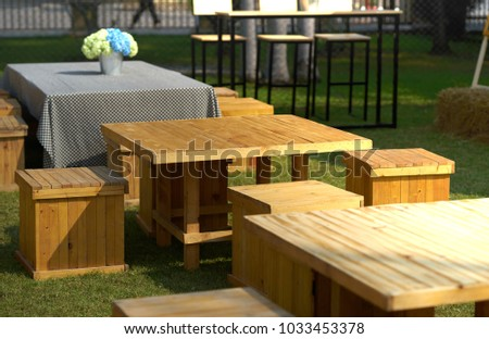 tables and chairs made by crate on grass garden with sunlight day time #1033453378