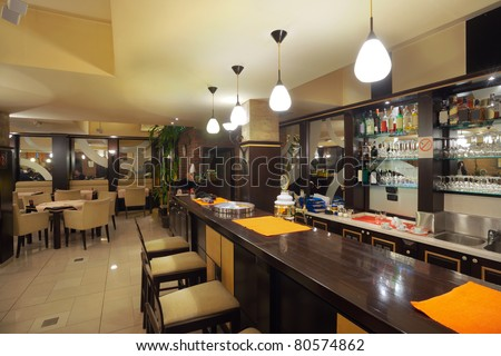 Tables, chairs, brick wall and lighting equipment of a restaurant.