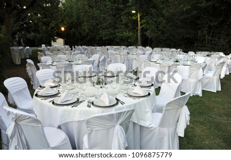 Tables prepared for the celebration of a romantic wedding banquet at night in an outdoor garden #1096875779